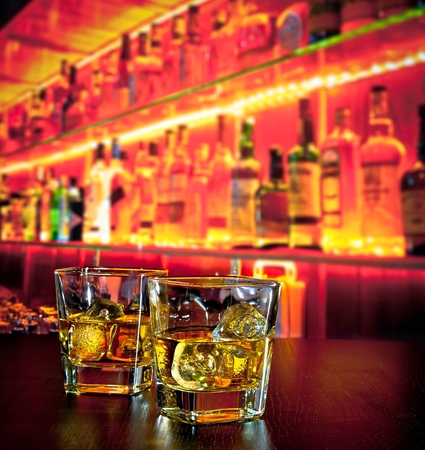 whisky: glasses of whiskey with ice on bar table near whiskey bottle on warm atmosphere lounge bar concept Stock Photo