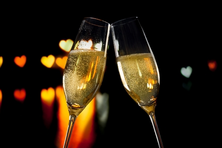 champagne flutes with golden bubbles make cheers on hearts bokeh background valentine day concept photo