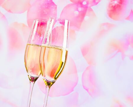 a pair of champagne flutes with golden bubbles on blur petals of roses background love concept photo