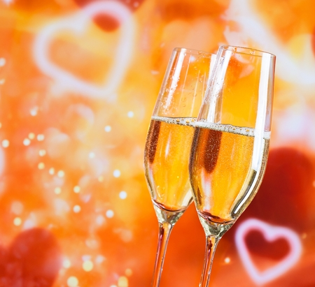 a pair of champagne flutes with golden bubbles on blur decorative hearts background love concept photo