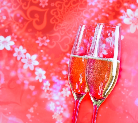 a pair of champagne flutes with golden bubbles on red vintage background love concept photo