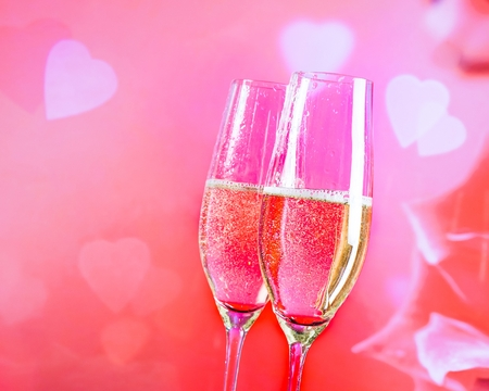 a pair of champagne flutes with golden bubbles on blur decorative hearts background photo