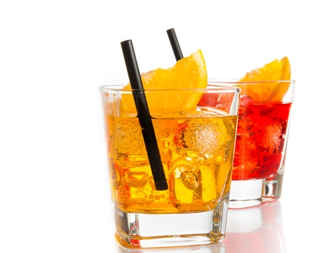 red and yellow cocktail with orange slice on top and straw isolated on white background with space for text photo