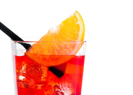 orange slice on top of the red cocktail with ice cubes and straw on white background, with space for text photo