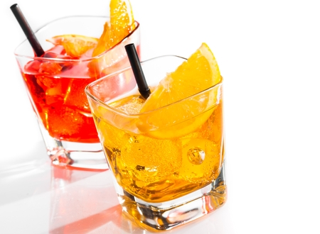 two cocktail with orange slice and straw on top isolated on white background with space for text photo