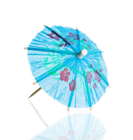 blue cocktail umbrella isolated against white background with reflection Reklamní fotografie