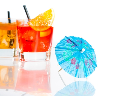 two cocktail with orange slice on top isolated behind blue umbrella on white background with space for text photo