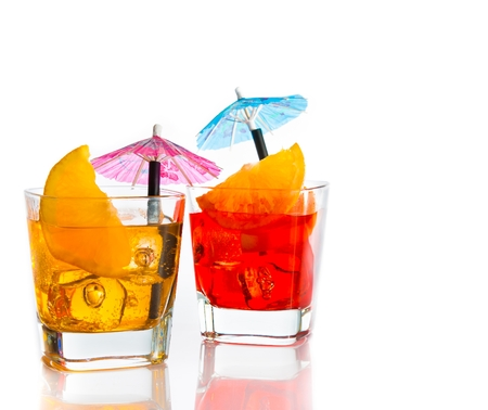 two cocktail with orange slice and umbrella on top isolated on white background with space for text photo