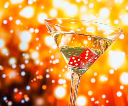 red dice in the cocktail glass on golden bokeh background