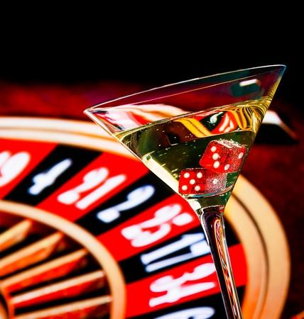 roulette: dadi rossi nel bicchiere da cocktail di fronte a ruota della roulette, serie casinò