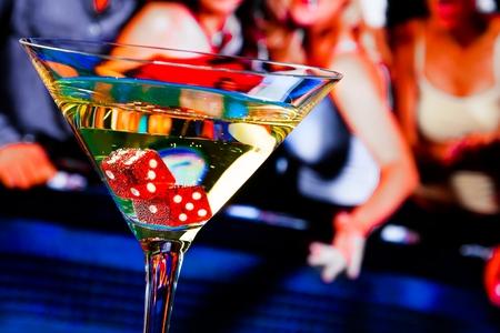 dados: dados rojos en la copa de c�ctel en frente de la mesa de juego, serie casino Foto de archivo