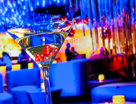 bar lounge: red dice in the cocktail glass in front of lounge bar casino, casino concept Stock Photo
