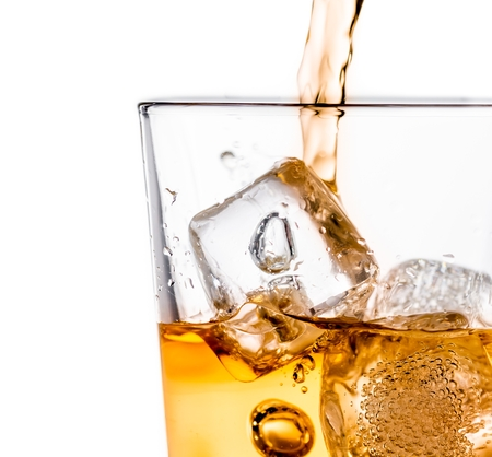 detail of pouring scotch whiskey in glass with ice cubes isolated on white background