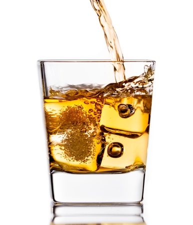 pouring scotch whiskey in glass with ice cubes isolated on white background