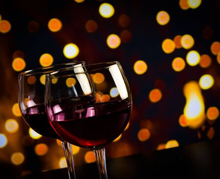 two red wine glasses on wood table against bokeh lights background, festive and fun concept photo