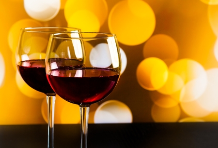 two red wine glasses on wood table against golden bokeh lights background, festive and fun concept