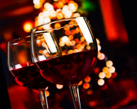 atmosphere: two red wine glass against christmas lights decoration background, christmas atmosphere