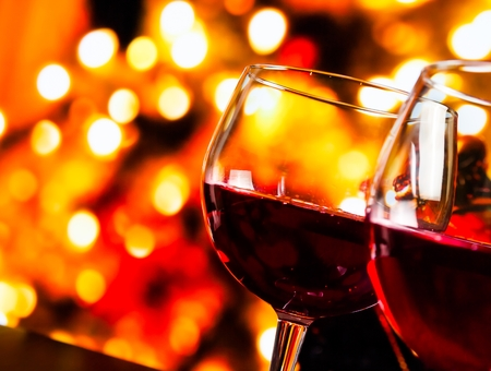 christmas atmosphere: red wine glasses against colorful unfocused lights background, festive and fun concept Stock Photo