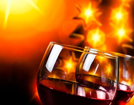 celebration background: two red wine glasses against golden lights tree background, christmas atmosphere