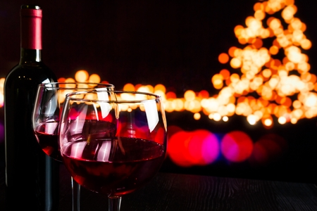 christmas atmosphere: red wine glass near bottle against bokeh lights background, christmas atmosphere Stock Photo