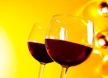 two red wine glasses against golden lights background, festive and fun concept photo
