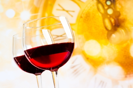 two red wine glasses against golden clock background, festive and fun concept photo