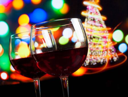 christmas atmosphere: red wine glass against bokeh lights tree background, christmas atmosphere