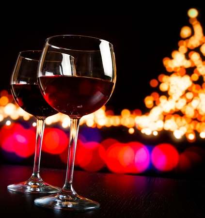 two red wine glass against bokeh lights tree background, christmas atmosphere