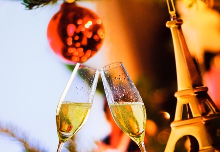 champagne flutes with golden bubbles make cheers on christmas eiffel decoration background, christmas paris atmosphere