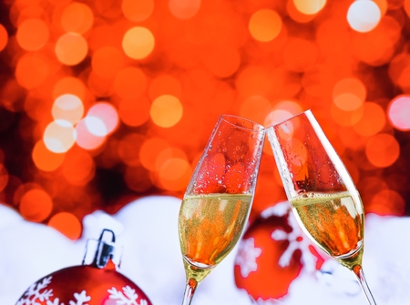 champagne flutes with golden bubbles make cheers on red christmas lights bokeh and balls decoration background, christmas atmosphere