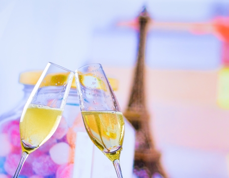 a pair of champagne flutes with golden bubbles make cheers on blur tower Eiffel background valentine day and love concept