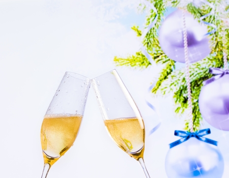 christmas atmosphere: champagne flutes with golden bubbles make cheers on christmas tree decoration background, christmas atmosphere Stock Photo