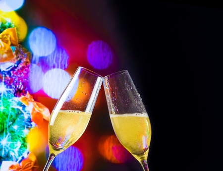 christmas atmosphere: champagne flutes with golden bubbles make cheers on christmas lights bokeh decoration background, christmas atmosphere
