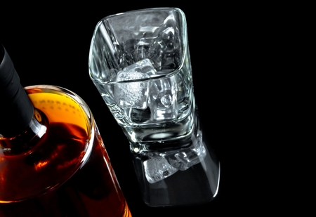intoxicant: top of view of empty whiskey glass with ice near bottle on black background, with reflection Stock Photo