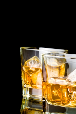 whiskey with ice in glasses on black background, with reflection photo
