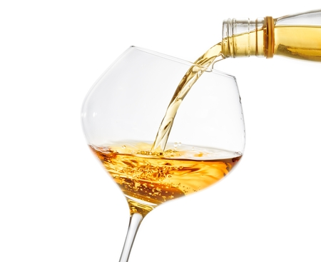pouring white wine into a glass on white background with space for text photo