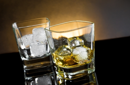 whiskey glasses with ice and warm light on black background, with reflection photo
