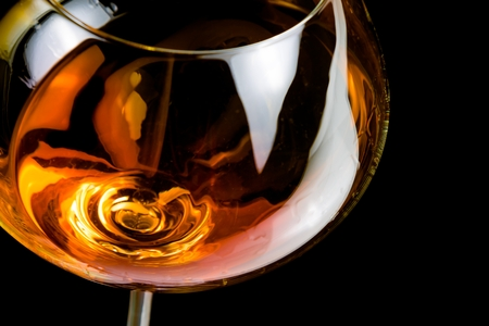 snifter of brandy in elegant glass with space for text on black background photo