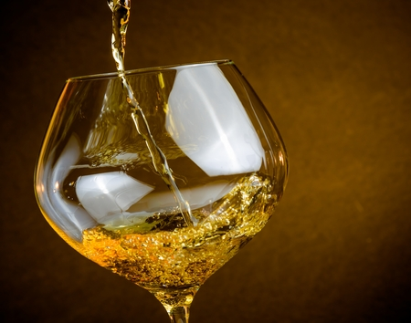 chairman: pouring white wine into a glass on golden background with space for text, warm atmosphere