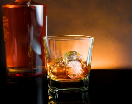 whiskey glass with ice and warm light on black table with reflection, warm atmosphere photo