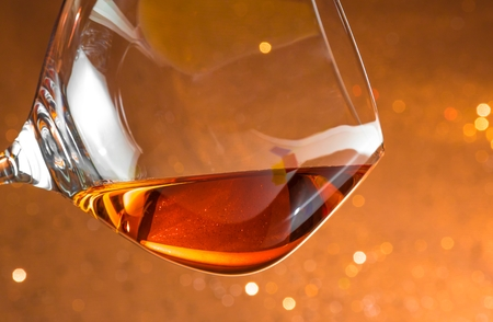 snifter of brandy in elegant glass with space for text on golden bokeh background