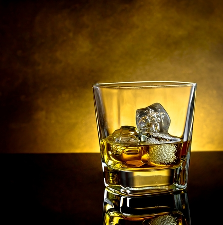 botella de whisky: vaso de whisky con hielo y c�lida luz en el cuadro negro con la reflexi�n y ambiente c�lido Foto de archivo