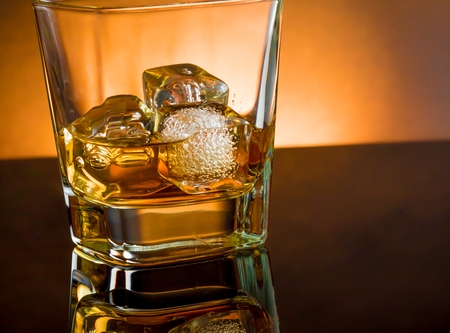 whiskey glass with ice and warm light on black table with reflection and warm atmosphere photo