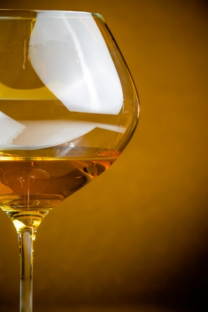 white wine into a glass on golden background with space for text, warm atmosphere photo
