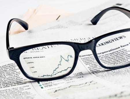 indexes: financial chart and graph of stock indexes see through glasses lens on financial newspaper, business concept