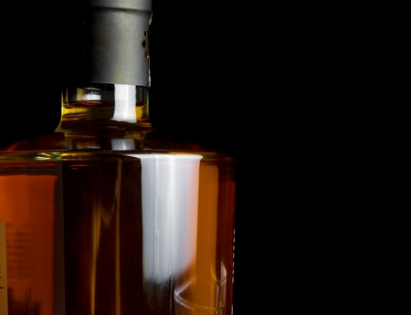 whiskey bottle on black background, with space for text