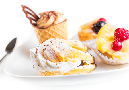 delicious little cream cake near cake with chocolate and fruit on white background photo