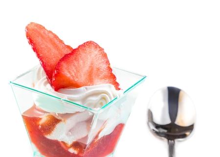 delicious strawberry cake with cream on white near a spoon photo