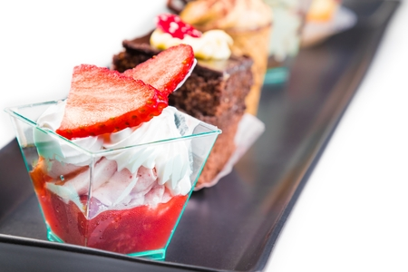 delicious strawberry cake with cream in front of little chocolate and coffee cakes on black dish photo