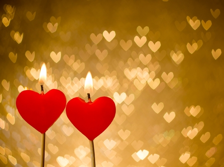 red hearts candles on golden hearts bokeh as background, valentine day and love concept